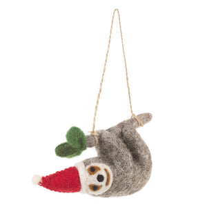 Grey felt sloth decoration hanging from a grey branch with green leaves and wearing a red Santa hat