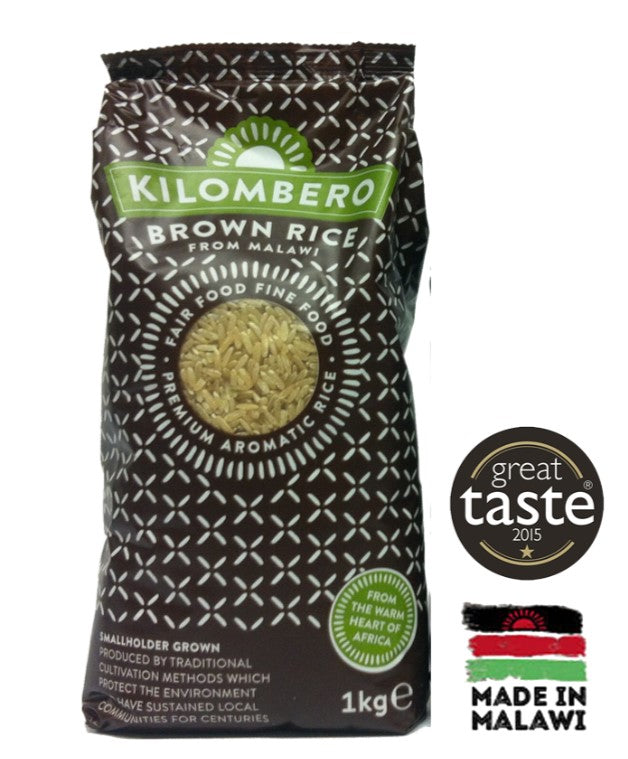 A bag of fair trade Kilombero brown rice in a black packet with green and white details. There is a Made in Malawi logo with red, green an black details from the national flag beside the packet