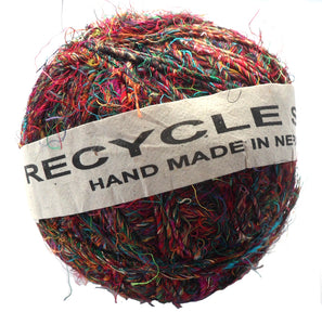 A ball of fair trade recycled sari silk yarn in shades of pink, orange, green an blue wrapped in a paper label.