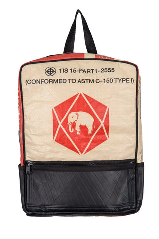 Fair trade, eco friendly, vegan backpack viewed from the front. The main panel is a red and cream cement bag with an elephant logo and the bottom is black recycled tyres. There is a front zip pocket and a black hanging strap