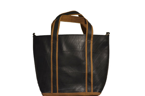 Front view of a fair trade recycled tyre tote bag. The bag is black with a texture from the tyre tread and mustard trim around the bottom of the bag and edging the straps.