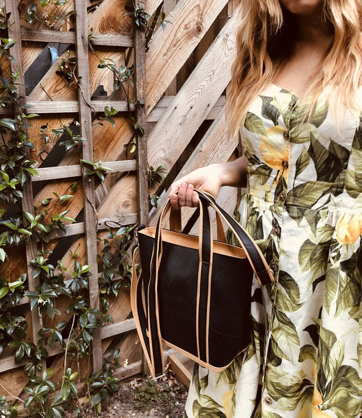 Fair trade recycled tyre black tote bag with mustard trim and lining being carried by a model with white skin and blond hair wearing a white dress with a green leaf and yellow flower pattern. She is stood against a trellis with leaves growing up it.