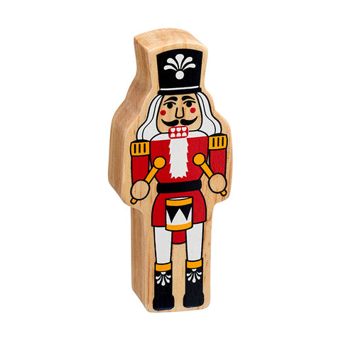 A nutcracker figure handpainted on chunky natural wood with the grain showing. He has a red coat with gold trim, black boots and hat and is holding a drum and drumsticks