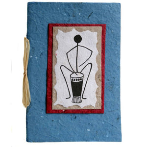 An eco friendly and fair trade greeting card witha black line drawing of an African drummer playing the drums on white handmade paper with irregular edges layered on rectangles of brown, and red paper then on blue card tied with twine