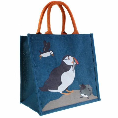 Fair trade eco-friendly jute bag in deep blue with a pattern of screen printed white, black and orange puffins on a grey rock