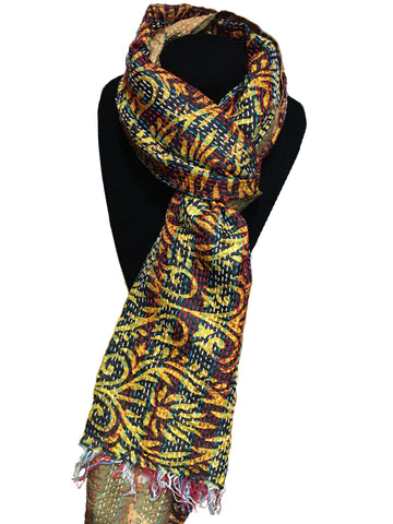 Fair trade kantha work scarf made from old saris. This scarf is displayed on a black stand and has red and blue stripes overlaid with a swirling gold pattern.