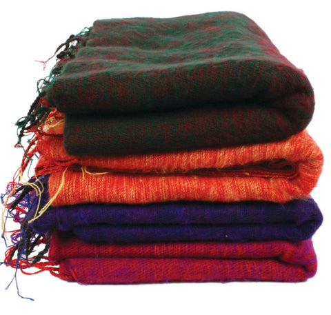 A pile of 4 fair trade recycled wool shawls. They are shades of purple blue, orange and black and all have tassels.