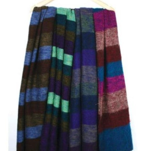 4 fair trade recycled wool shawls hanging from a wooden coat hanger. They are shades of purple blue, brown and green.