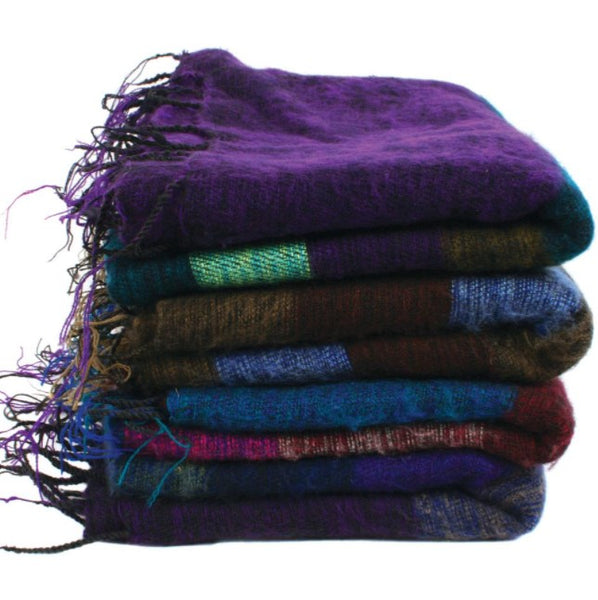 A pile of 4 fair trade recycled wool shawls. They are striped with various thickness of stripes and are shades of purple, blue, brown and green and all have tassels.