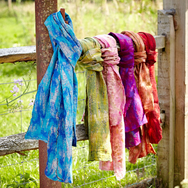 A group of six fair trade silk and felt scarves tied on a fencepost with a meadow in the background. The scarf in the foreground is shades of blue and there are green, pink, purple, orange and red scarves behind it.