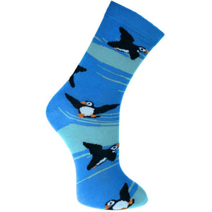Fair trade bamboo socks with a pattern of black, white and yellow puffins on a dark and light blue sea background.