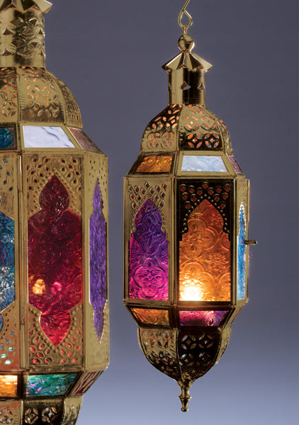 Gold coloured metalwork lantern with multicolour glass panels illuminated by a t-light on a dark grey background