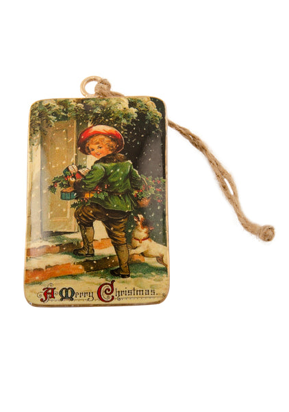 A rectangular tin Christmas decoration showing a vintage scene of a boy and a dog going into a house laden with Christmas gifts. Main colours are green and red