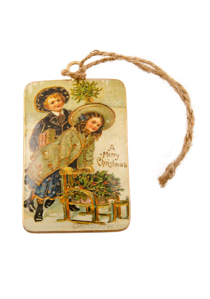 A rectangular tin Christmas decoration showing a vintage scene of a boy and girl with a sledge full of holly. Main colours are green and ivory