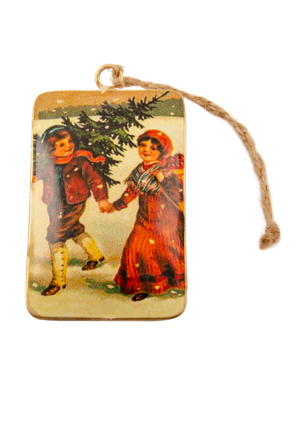 A rectangular tin Christmas decoration showing a vintage scene of a boy and girl carrying a Christmas tree. Main colours are red and green