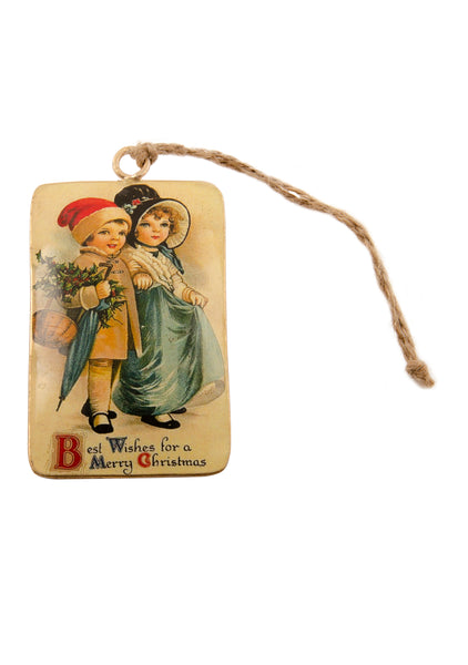 A rectangular tin Christmas decoration showing a vintage scene of a smartly dressed girl and a boy in a Santa hat carrying holly and an umbrella. Main colours are blue and gold