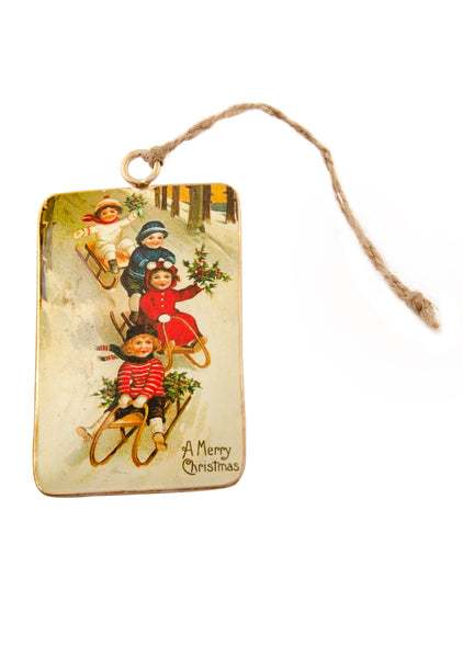 A rectangular tin Christmas decoration showing a vintage scene of four children sledging down a hill. Main colours are red and blue