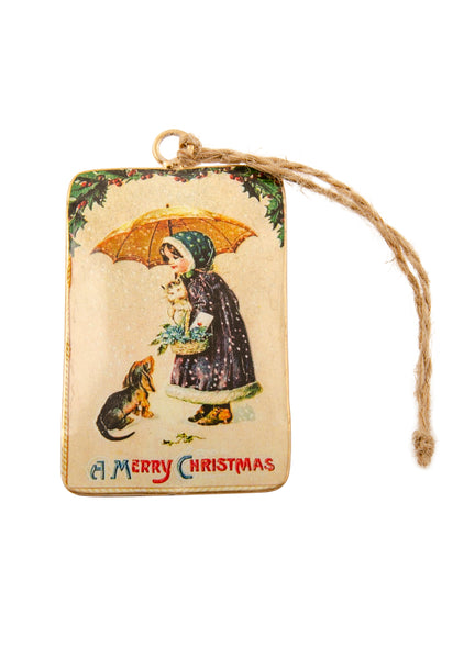 A rectangular tin Christmas decoration showing a vintage scene of a girl with a kitten and a dog under an umbrella in the snow. Main colours are blue and gold