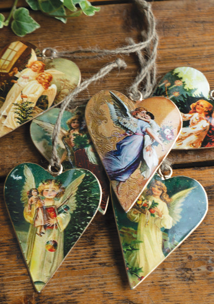 A set of six heart shaped tin Christmas decorations with vintage pictures of angels, on a wooden background