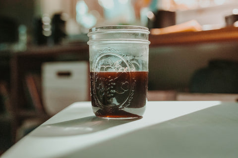 Cold brewed coffee in a mason jar sitting on a table in the sunlight