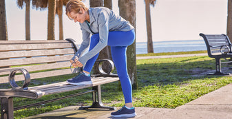 woman tying her cheeks multisport shoe lace on park bench