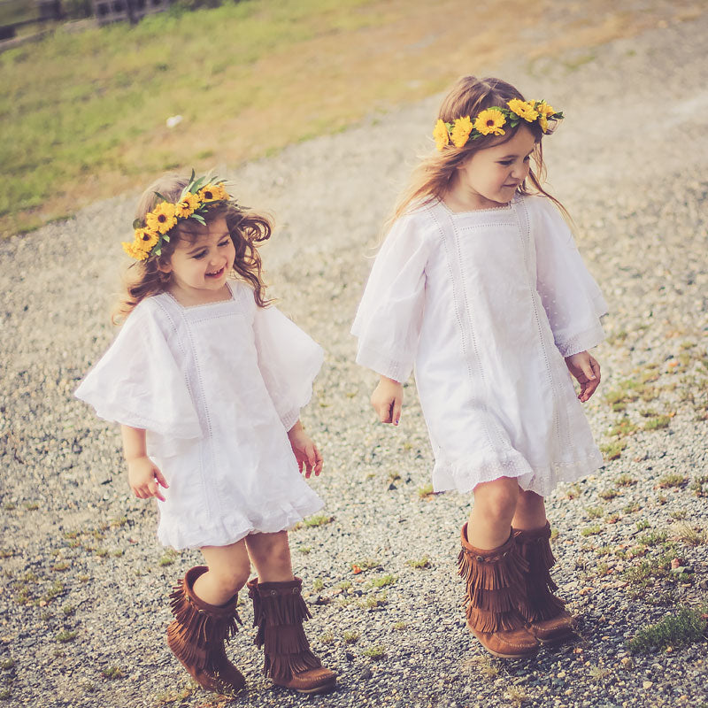 Two young girls wearing summer head wreaths featuring mini bright yellow Viking poms with look like extra tiny Sunflowers, accented with a touch of greenery.