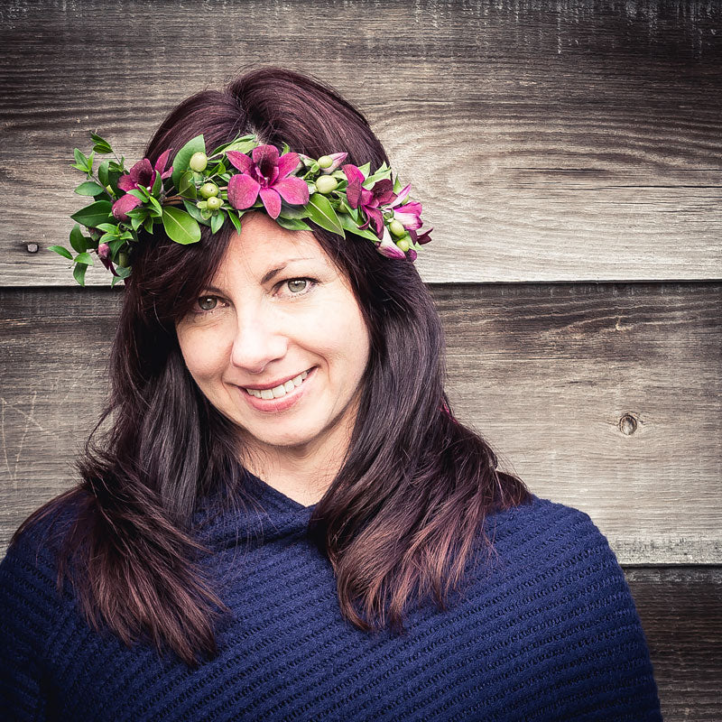 Lady wearing a flower head wreath with pink Cymbidium Orchids with mixed foliage accents.