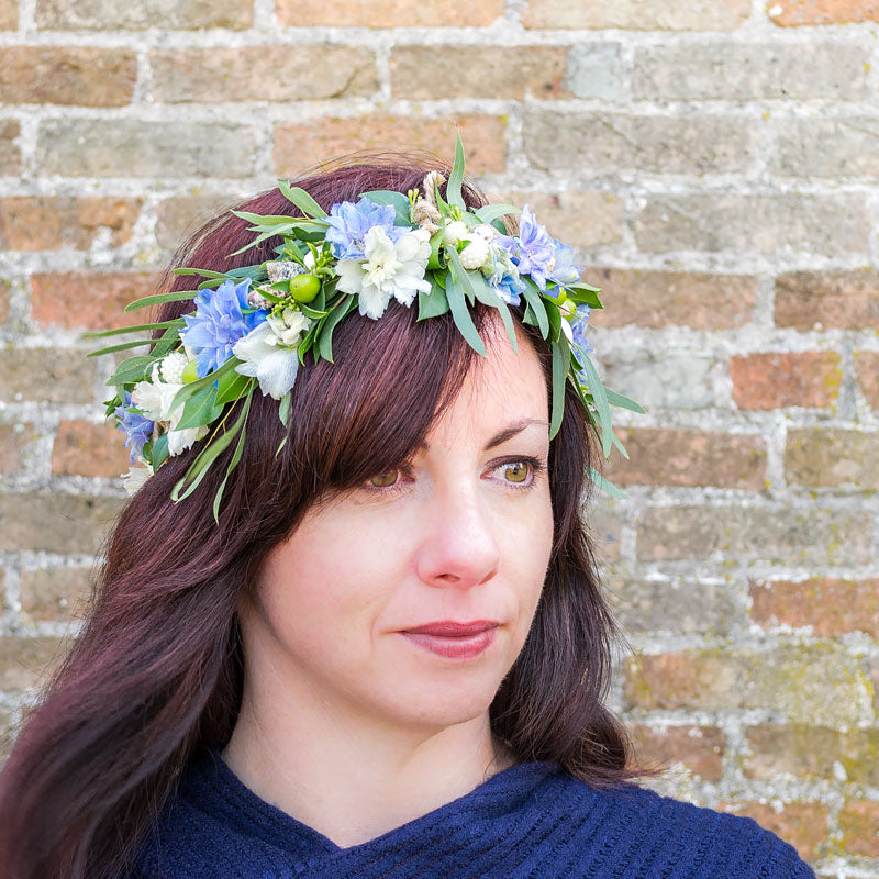 Young woman wearing a flower crown with blue Delphinium blooms and Eucalyptus accents.