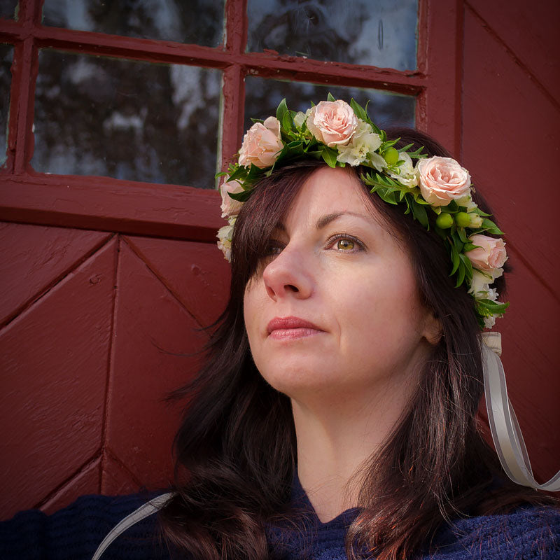 Lady wearing a head wreath with soft pink  mini Roses accented with tiny greenery.