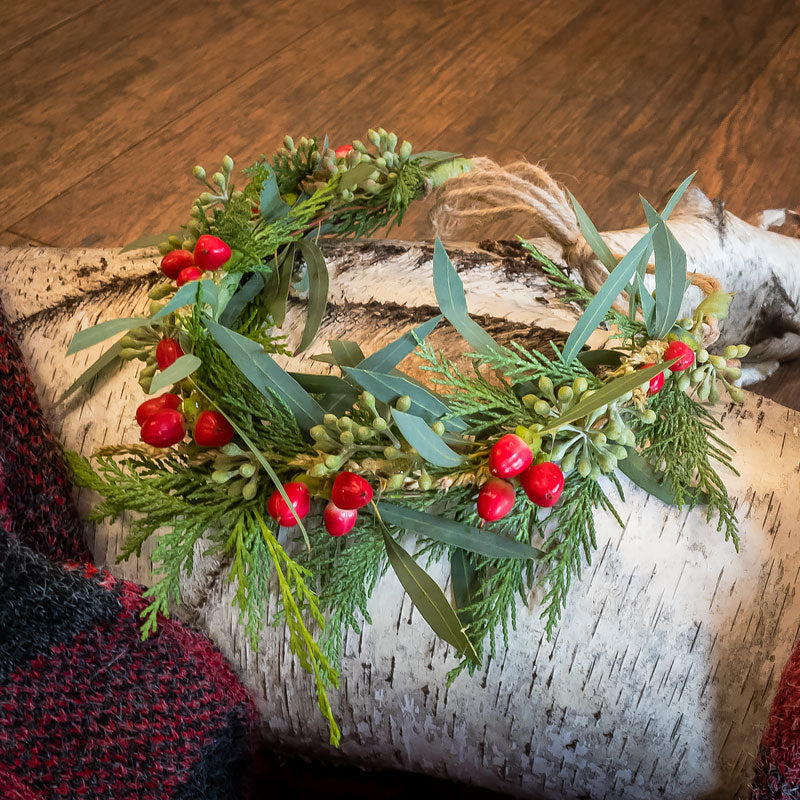 A simple yet elegant Christmas flower head wreath with red berries, Eucalyptus, and seasonal greenery.