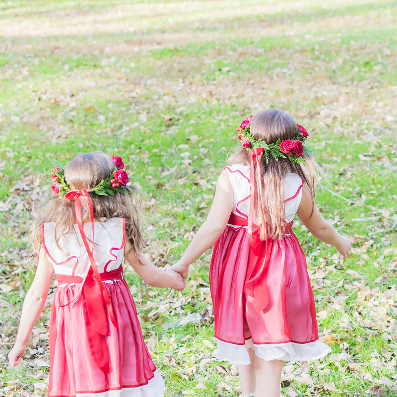 Two young girls wearing Christmas flower crowns with mini red Roses, Berries, and seasonal greens ,ade to match their bright red holiday dresses.