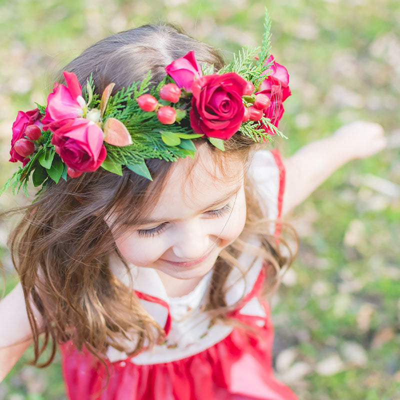 Close up of a young girl and her Christmas flower head wreath with min red Roses and holiday greenery accents.