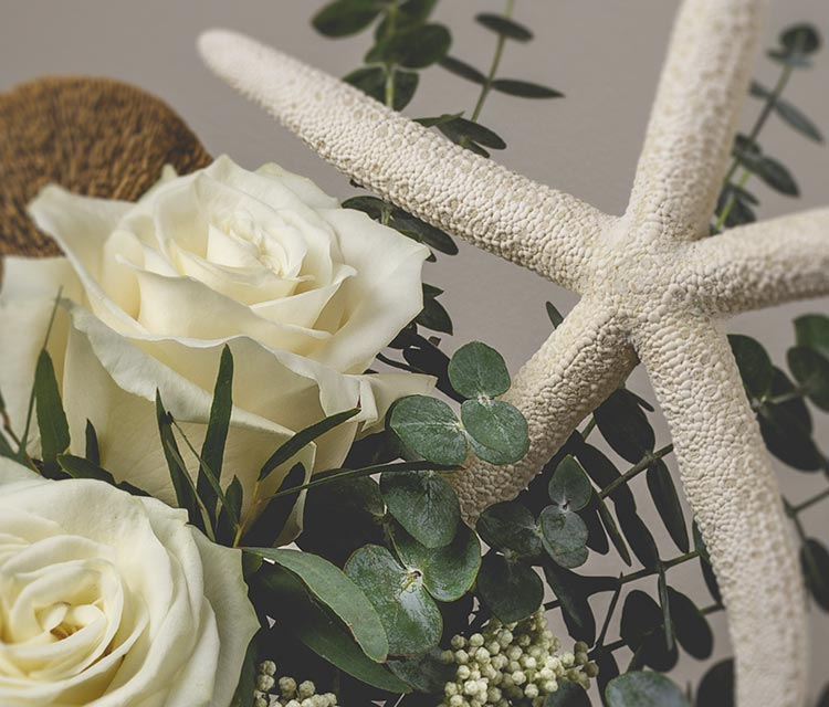 Nautical themed floral arrangement with white roses, eucalyptus and a large starfish accent