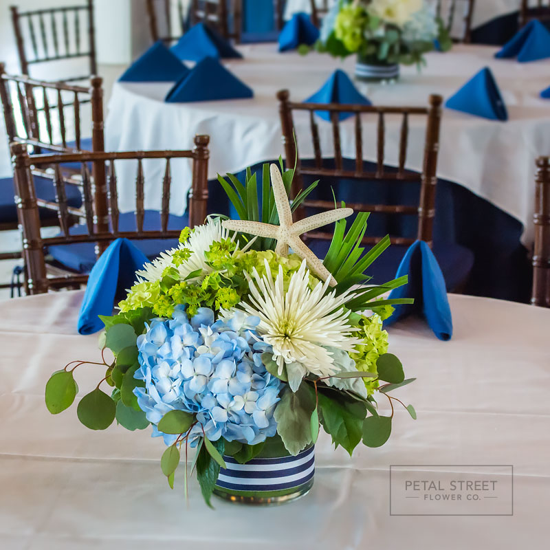 Nautical themed table centerpieces with a mix of blue and green Hydrangea, Fan Palm foliage, and Starfish accents.