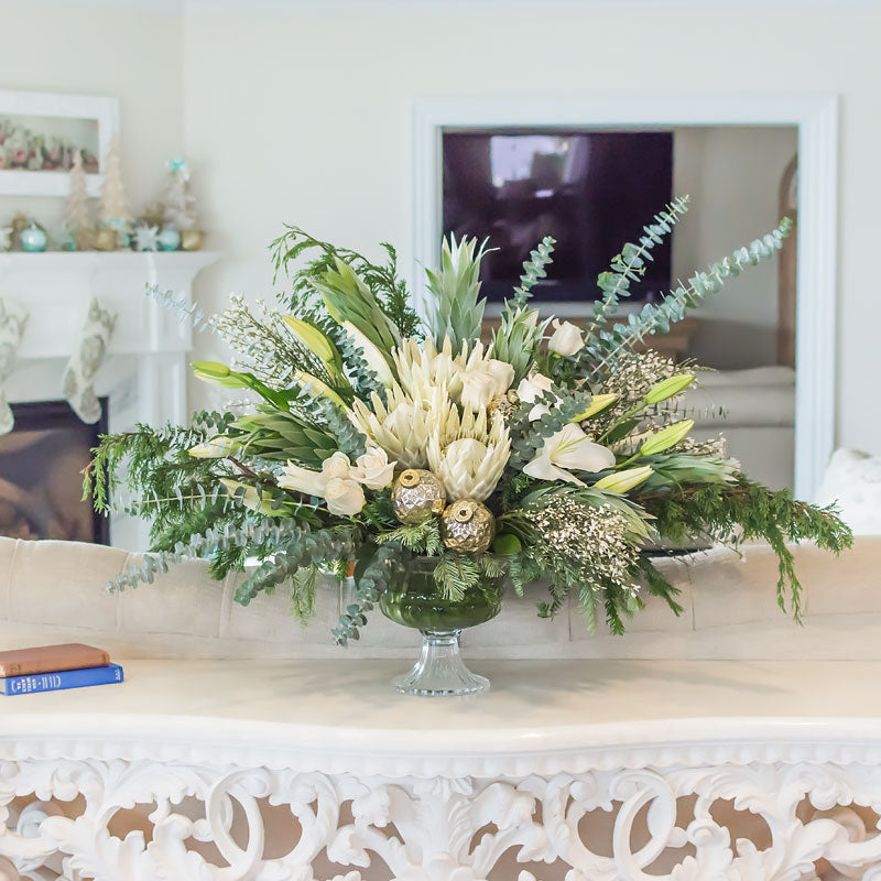 Gorgeous Christmas centerpiece with white Roses, large King Protea, Lilies, Cedar and eucalyptus foliage, and antique holiday ornaments throughout.