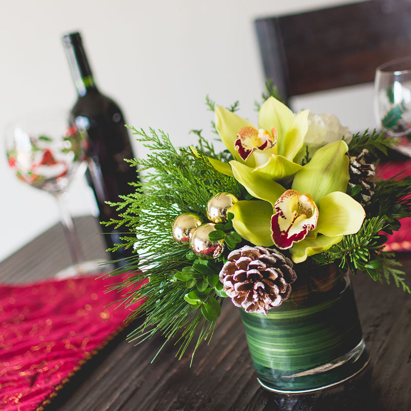 Mini table centerpieces for Christmas season with soft Pine greenery, green Cymbidium Orchids, Pine Cone and holiday ornament accents.