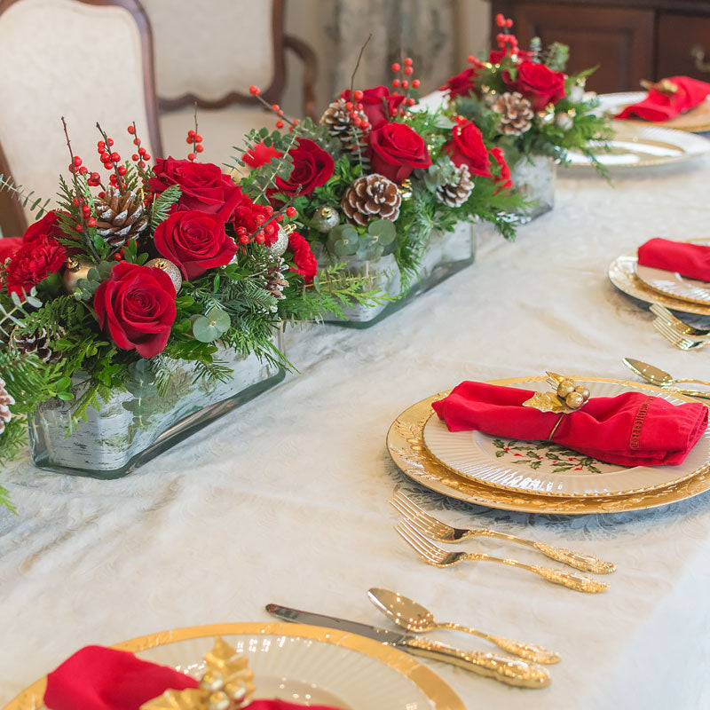 Extra long Christmas table centerpiece with a mix of seasonal greenery, mini Pine Cones, mini holiday ornaments, and bright red Roses and Berries.