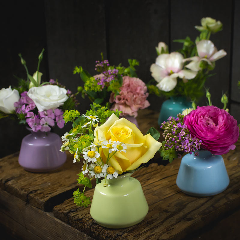 A variety of mini bud vase table settings each with a different bright colored flower and accent for a simple yet exciting table scape when viewed together.