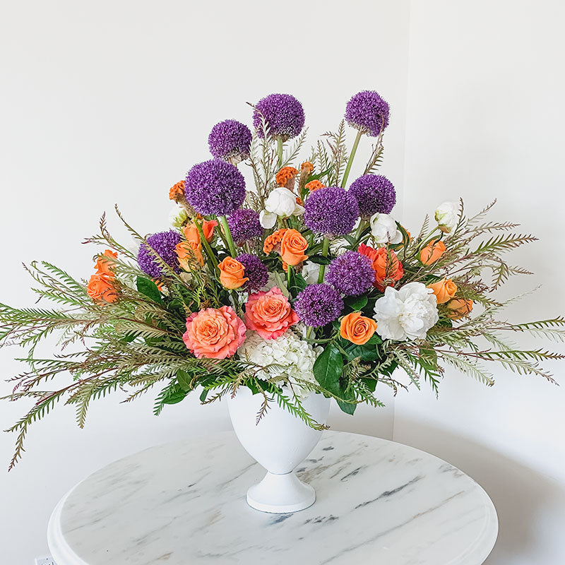 Large table centerpiece by Petal Street Flower Company florist featuring bright orange Roses, Celosia, white Peonies, purple Allium, and Hydrangea.