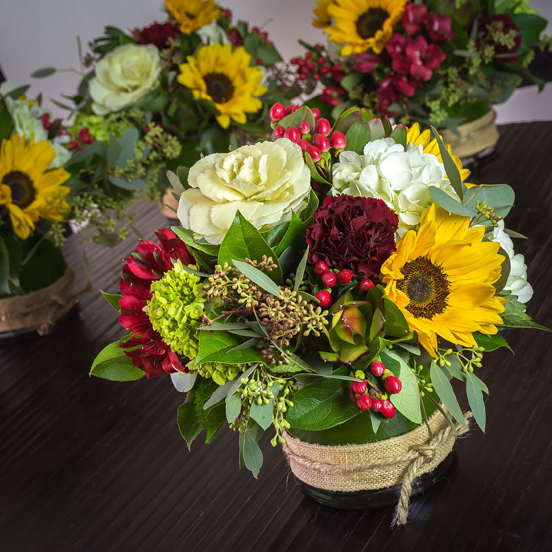 Autumn theme table centerpieces featuring Kale, Sunflowers, Eucalyptus, and Alstroemeria in low glass cylinders with a burlap collar accent.