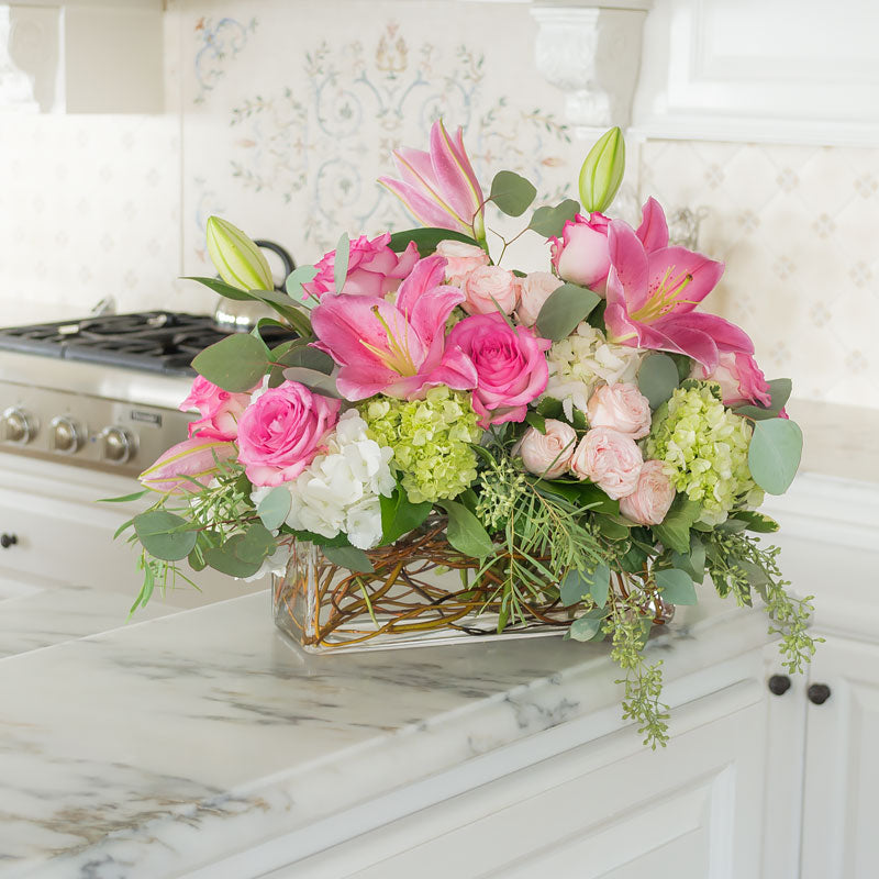 Elegant centerpiece arrangement in a low wide rectangular vase with Roses, Lilies, and Hydrangea in mixed pink and white colors and Curly Willow accents.