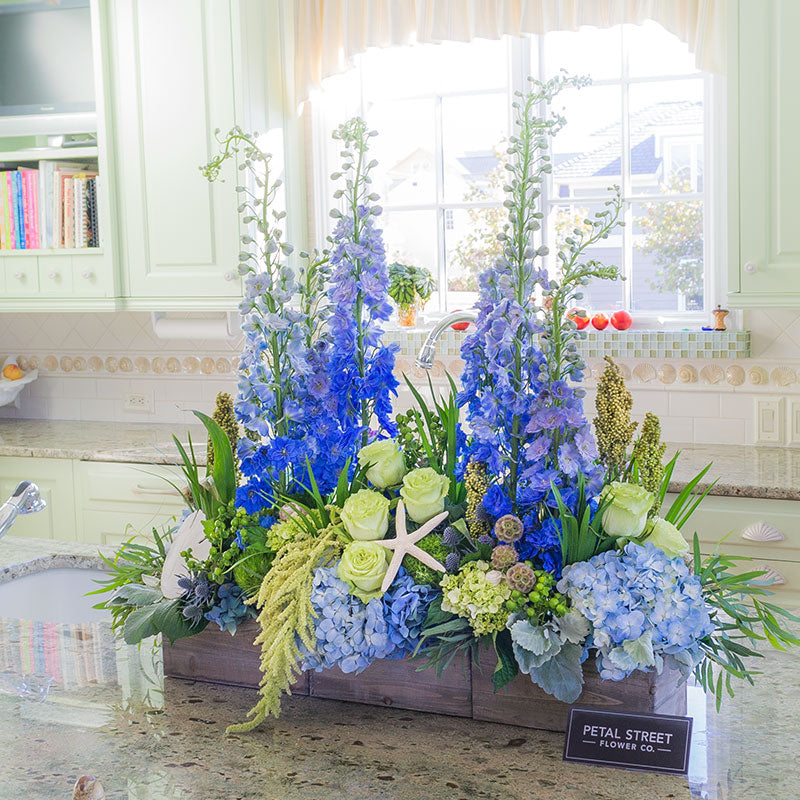 Large nautical table centerpiece in driftwood styled box with a mix of blue and green flowers featuring Delphinium, Roses, Hydrangea, Amaranthus, Hypericum Berries, Sea Shells, and Starfish.