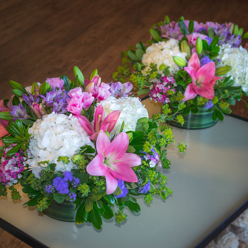 Table arrangement in low extra wide glass cylinders with pink Lilies, white Hydrangea, Bupleurum, Ageratum, and greenery accents.