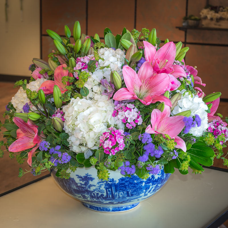 Large centerpiece arranged in a ceramic family heirloom bowl with pink Lilies, Sweet William, Hydrangea, Ageratum, Bupleurum, and greenery accents.