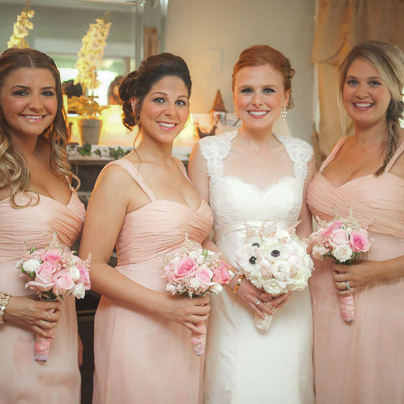 Bride and Bride's Maids holding bouquets of soft pink and white flowers.