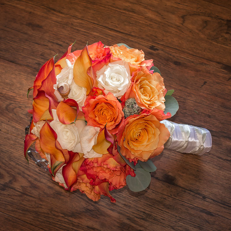Nautical themed bride bouquet with a mix of Roses in coral colors with small sea shell accents throughout.