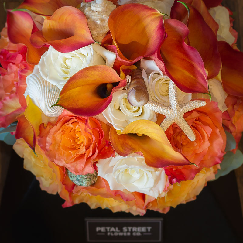 Close up of a nautical themed bride's bouquet with coral Roses and sea shell accents.