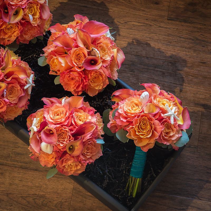 Nautical inspired bride's maids bouquets with coral colored Roses and sea shell accents.