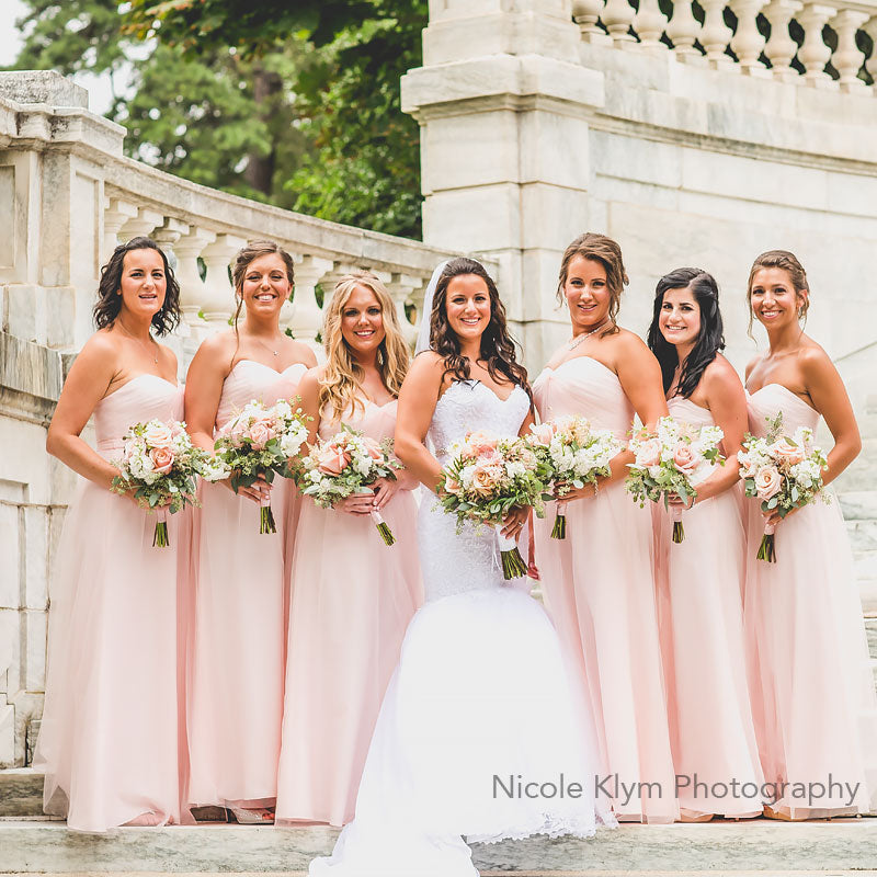 Bride and her bride's maids posing atop a large staircase with their bouquets of soft blush colors.