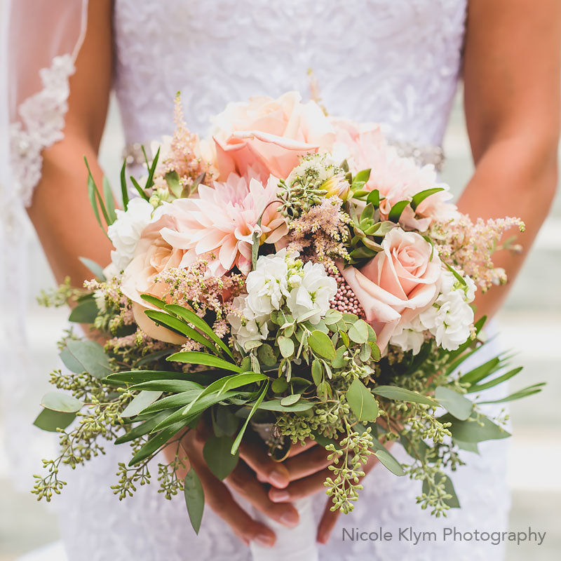 Bridal bouquet with a mixed of soft colored flower such as Dhalias and Roses accented with Eucalyptus.